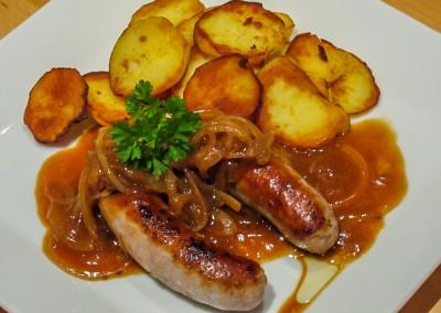 Bratwurst mit Zwiebelsoße Bratkartoffeln und Salat