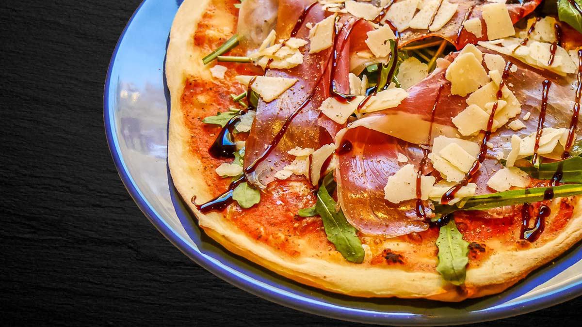 Pizza mit Parma-Schinken und Rucola