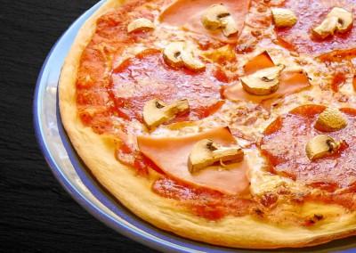 Selbstgemachte Pizza mit Salami, gekochten Schinken und frischen Champignons